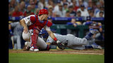 Los Angeles Dodgers' Austin Barnes, right, steals home past Philadelphia Phillies catcher J.T. Realmuto, left, during the fourth inning of a baseball game, Monday, July 15, 2019, in Philadelphia. (AP Photo/Matt Slocum)