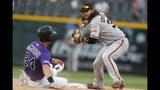 El campocorto de los Gigantes de San Francisco, Brandon Crawford, derecha, se apresta a tirar a primera base tras forzar el out en segunda base del jugador de los Rockies de Colorado, Ryan McMahon (24), en el noveno inning de un juego de béisbol, el lunes 15 de julio de 2019, en Denver. (AP Foto/David Zalubowski)