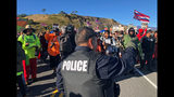 A police officer gestures at demonstrators blocking a road at the base of Hawaii's tallest mountain, Monday, July 15, 2019, in Mauna Kea, Hawaii, who are protesting the construction of a giant telescope on land that some Native Hawaiians consider sacred. (AP Photo/Caleb Jones)