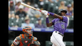 Colorado Rockies pinch-hitter Raimel Tapia, right, follow the flight of his solo home run with San Francisco Giants catcher Buster Posey in the sixth inning of a baseball game Monday, July 15, 2019, in Denver.(AP Photo/David Zalubowski)