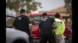 In this July 8, 2019, photo, a U.S. Immigration and Customs Enforcement (ICE) officers detain a man during an operation in Escondido, Calif. The carefully orchestrated arrest last week in this San Diego suburb illustrates how President Donald Trump's pledge to start deporting millions of people in the country illegally is virtually impossible with ICE's budget and its method of picking people up. (AP Photo/Gregory Bull)