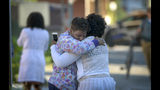 Two women embrace in an alley behind the Man Alive drug treatment center in Baltimore shortly after a shooting. At least two people are dead and a police sergeant and a woman are injured following a shooting at a methadone clinic in Baltimore, police said Monday. (Jerry Jackson/The Baltimore Sun via AP)