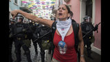 A woman gives a thumbs down where police block demonstrators from advancing to La Fortaleza governor's residence in San Juan, Puerto Rico, Sunday, July 14, 2019. Protesters are demanding Gov. Ricardo Rosselló step down for his involvement in a private chat in which he used profanities to describe an ex-New York City councilwoman and a federal control board overseeing the island's finance. (AP Photo/Carlos Giusti)