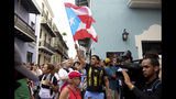 A man waves a Puerto Rican flag during a protest near La Fortaleza governor's residence in San Juan, Puerto Rico, Sunday, July 14, 2019. Protesters are demanding Gov. Ricardo Rosselló step down for his involvement in a private chat in which he used profanities to describe an ex-New York City councilwoman and a federal control board overseeing the island's finance. (AP Photo/Carlos Giusti)