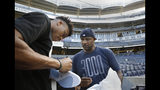 Milwaukee Bucks forward and 2019 NBA Most Valuable Player Giannis Antetokounmpo, left, signs shoes for New York Yankees starting pitcher CC Sabathia before a baseball game between the Yankees and the Tampa Bay Rays, Monday, July 15, 2019, in New York. (AP Photo/Kathy Willens)