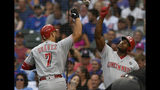 Cincinnati Reds' Eugenio Suarez (7) celebrates with teammate Yasiel Puig, right, at home plate after hitting a solo home run during the first inning of a baseball game against the Chicago Cubs, Monday, July 15, 2019, in Chicago. (AP Photo/Paul Beaty)
