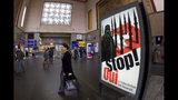 FILE - In this Nov. 4, 2009, file photo, people walk by a poster from the right-wing Swiss People's Party (SVP/UDC) depicting a woman wearing a burqa in front of a Swiss flag upon which are minarets which resemble missiles, at the central station in Geneva, Switzerland. Later in the month, a successful referendum banned the construction of new minarets in the country. (Salvatore Di Nolfi/Keystone via AP, File)