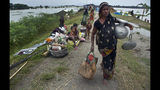 An Indian flood affected woman carries her belongings on an embankment to take shelter in Pabhokathi village east of Gauhati India, Monday, July 15, 2019. After causing flooding and landslides in Nepal, three rivers are overflowing in northeastern India and submerging parts of the region, affecting the lives of more than 2 million, officials said Monday.(AP Photo/Anupam Nath)