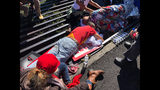 Activist Walter Ritte, left, and others lay chained to a cattle grate blocking a road at the base of Hawaii's tallest mountain, Monday, July 15, 2019, in Mauna Kea, Hawaii, protesting the construction of a giant telescope on land that some Native Hawaiians consider sacred. (AP Photo/Caleb Jones)