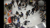 In this Sunday, July 14, 2019, photo, protesters throw umbrellas toward policemen during a crash inside a shopping mall in Sha Tin District in Hong Kong. What began as a protest against an extradition bill has ballooned into a fundamental challenge to the way Hong Kong is governed _ and the role of the Chinese government in the city's affairs. (AP Photo/Kin Cheung)