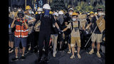 In this Sunday, July 14, 2019, photo, protesters wearing protection gears as they prepare to face-off with policemen on a street in Sha Tin District in Hong Kong. What began as a protest against an extradition bill has ballooned into a fundamental challenge to the way Hong Kong is governed _ and the role of the Chinese government in the city's affairs. (AP Photo/Kin Cheung)