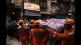 Rescuers carry the body of a victim at the site of a building that collapsed in Mumbai, India, Tuesday, July 16, 2019. A four-story residential building collapsed Tuesday in a crowded neighborhood in Mumbai, India's financial and entertainment capital, and several people were feared trapped in the rubble, an official said. (AP Photo/Rafiq Maqbool)