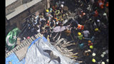 Rescuers carry the body of a victim at the site of a building that collapsed in Mumbai, India, Tuesday, July 16, 2019. A four-story residential building collapsed Tuesday in a crowded neighborhood in Mumbai, India's financial and entertainment capital, and several people were feared trapped in the rubble, an official said. (AP Photo/Rajanish Kakade)