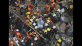 Rescuers carry out a survivor from the site of a building that collapsed in Mumbai, India, Tuesday, July 16, 2019. A four-story residential building collapsed Tuesday in a crowded neighborhood in Mumbai, India's financial and entertainment capital, and several people were feared trapped in the rubble, an official said.(AP Photo/Rajanish Kakade)
