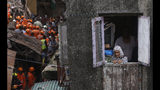 A woman looks from a window as rescuers work at the site of a building that collapsed in Mumbai, India, Tuesday, July 16, 2019. A four-story residential building collapsed Tuesday in a crowded neighborhood in Mumbai, India's financial and entertainment capital, and several people were feared trapped in the rubble, an official said. (AP Photo/Rafiq Maqbool)