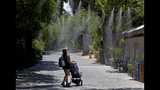 Visitors keep cool under misters at the Phoenix Zoo, Tuesday, July 16, 2019, in Phoenix. The National Weather Service has issued an excessive heat warning to take effect until Wednesday night. The Phoenix Zoo uses spraying, frozen treats and shaded area's to keep their animals cool. (AP Photo/Matt York)