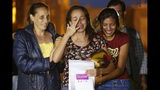 Karen Palacios, center, is helped by family members after she was released from prison at Los Teques on the outskirts of Caracas, Venezuela, Tuesday, July 16, 2019. Palacios who plays the clarinet and was cut from the National Philharmonic for criticizing the government, was detained for 6 weeks. (AP Photo/Ariana Cubillos)