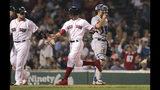 El jugador de los Medias Rojas de Boston, Mookie Betts, centro, y su compañero, el puertorriqueño Christian Vázquez, anotan en un sencillo del dominicano Rafael Devers durante el cuarto inning de un juego de béisbol contra los Azulejos de Toronto, en Boston, el miércoles 17 de julio de 2019. (AP Foto/Charles Krupa)