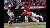 Los Angeles Angels' Kole Calhoun, right, scores past Houston Astros catcher Max Stassi on a three-run double by Albert Pujols during the first inning of a baseball game Tuesday, July 16, 2019, in Anaheim, Calif. (AP Photo/Marcio Jose Sanchez)