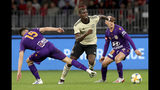 Manchester United's Paul Pogba, centre, challenges for the ball with unidentified Perth Glory players, during their friendly soccer match in Perth, Australia, Saturday, July 13, 2019. (Richard Wainwright/AAP Image via AP)