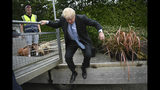 Conservative Party leadership candidate Boris Johnson jumps down from a trailer during a visit to King & Co tree nursery, in Braintree, Essex, ahead of a Tory leadership hustings, England, Saturday, July 13, 2019. (Neil Hall/Pool photo via AP)
