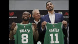 Newly acquired Boston Celtics guard Kemba Walker (8) and center Enes Kanter (11) pose with their team jerseys at the Celtics' basketball practice facility, Wednesday, July 17, 2019, in Boston. Looking on is team general manager Danny Ainge. (AP Photo/Elise Amendola)