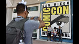 FILE - In this Wednesday, July 18, 2018, file photo, Luis Ramos, left, of San Diego takes a picture of his son Alek, third from right, and daughter Anabel, second from right, and their friends Emiliano Beltran, fourth from right, and Isabel Beltran, before Preview Night at Comic-Con International at the San Diego Convention Center, in San Diego. The four-day 2019 Comic-Con kicks off Wednesday, July 17, 2019, when the showroom floor opens to thousands vying for exclusive merchandise. (Photo by Chris Pizzello/Invision/AP, File)