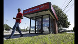 In this Monday, July 15, 2019 photo a customer departs a Bank of America ATM, in Norwood, Mass. Bank of America Corp. reports earnings Wednesday, July 17. (AP Photo/Steven Senne)