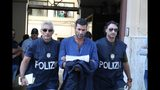Suspect Antonino Lo Presti, center, is taken into custody during an anti-mafia operation lead by the Italian Police and the FBI in Palermo, Southern Italy, Wednesday, July 17, 2019. Italian police and the FBI arrested 19 suspected Mafiosi in a joint operation Wednesday following an investigation which revealed alleged ties between Sicily's Cosa Nostra Mafia and New York's Gambino crime family. (Igor Petix/ANSA Via AP)