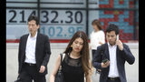 People walk by an electronic stock board of a securities firm in Tokyo, Wednesday, July 17, 2019. Asian stocks were mixed Wednesday as Wall Street ended a five-day winning streak after the first big round of corporate earnings reports. (AP Photo/Koji Sasahara)
