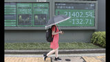A woman walks by an electronic stock board of a securities firm in Tokyo, Wednesday, July 17, 2019. Asian stocks were mixed Wednesday as Wall Street ended a five-day winning streak after the first big round of corporate earnings reports. (AP Photo/Koji Sasahara)