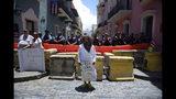 Una persona vestida como Jesucristo sostiene un cartel enfrente de un cordón policial alrededor de la residencia oficial del gobernador Ricardo Rosselló en San Juan, Puero Rico, el miércoles 17 de julio de 2019. (AP Foto/Carlos Giusti)