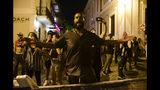 Ciudadanos cerca de la mansión ejecutiva exigen la renuncia del gobernador Ricardo Rosselló en San Juan, Puerto Rico, el lunes 15 de julio de 2019. (AP Foto/Carlos Giusti)