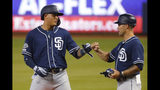 San Diego Padres' Manny Machado, left, is congratulated by third base coach Glenn Hoffman after getting a base hit during the first inning the team's baseball game against the Miami Marlins, Wednesday, July 17, 2019, in Miami. (AP Photo/Wilfredo Lee)