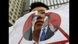 A protester holds a defaced image of Japanese Prime Minister Shinzo Abe during a rally denouncing the Japanese government's decision on their exports to South Korea in front of the Japanese Embassy in Seoul, Wednesday, July 17, 2019. In his strongest comments yet on a growing trade dispute, South Korean President Moon Jae-in urged Japan on Monday to lift recently tightened controls on high-tech exports to South Korea, which he said threaten to shatter the countries' economic cooperation and could damage Japan more than South Korea. (AP Photo/Ahn Young-joon)
