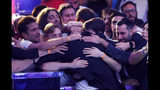 Supporters embrace Dario Sammartino, of Italy, center facing away from camera, after he was eliminated at the final table of the World Series of Poker main event, Wednesday, July 17, 2019, in Las Vegas. Sammartino finished the tournament in second place. (AP Photo/John Locher)