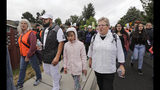 In this photo taken Wednesday, July 17, 2019, Jose Robles, second left, walks with Gethsemane Lutheran Church Pastor Joanne Engquist, right, and hundreds of supports as Robles walks to present himself to himself U.S. Immigration and Customs Enforcement officials in Tukwila, Wash. The prospect of nationwide immigration raids has provided evidence that legions of pastors, rabbis and their congregations stand ready to help vulnerable immigrants with offers of sanctuary and other services. (AP Photo/Elaine Thompson)