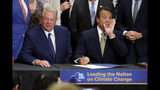 New York Gov. Andrew Cuomo, right, accompanied by former Vice President Al Gore, announces that he is signing the Climate Leadership and Community Protection Act, Thursday, July 18, 2019, at Fordham University in New York. New York's new law aimed at ending climate change emissions will drive dramatic changes over the next 30 years if it meets its ambitious goals. (AP Photo/Richard Drew)