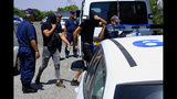 Cyprus police officers escort two of the twelve Israelis who have been detained, in Paralimni town, Cyprus, Thursday, July 18, 2019. A Cyprus court has ordered that 12 Israelis vacationing on the east Mediterranean island nation remain in police custody for 8 days after a 19 year-old British woman alleged that she was raped. (AP Photo/Petros Karadjias)