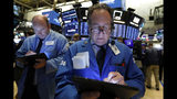 FILE - In this June 19, 2019, file photo trader Steven Kaplan, right, works on the floor of the New York Stock Exchange. The U.S. stock market opens at 9:30 a.m. EDT on Thursday, July 18. (AP Photo/Richard Drew, File)