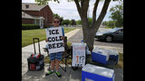 """In this Tuesday, July 16, 2019 photo provided by the Brigham City Police Department, Seth Parker stands at his soda stand in Brigham City, Utah. Parker is earning widespread social media attention for his neighborhood soda stand thanks to a sign he holds that reads, """"Ice cold beer"""" with """"root"""" above the word beer in tiny print. Brigham City Police Lt. Tony Ferderber said Thursday, July 18, 2019, that several residents in the northern Utah city called police concerned about a young boy selling alcohol in front of a church. Officers realized that it was just a clever marketing ploy and posted pictures of 11-year-old Seth Parker on Facebook with the comment, """"a twist on a lemonade stand."""" (Brigham City Police Department via AP)"""