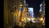 En esta fotografía del miércoles 17 de julio de 2019, un manifestante envuelto con la bandera puertorriqueña es sostenido en alto alto por otro inconforme durante una movilización y enfrentamientos en San Juan, Puerto Rico. Miles de personas marcharon hacia la residencia del gobernador Ricardo Roselló exigiendo su renuncia después de que se filtrara el contenido de un chat en el que hizo referencias misóginas y se burló de sus electores. (AP Foto/Dennis M. Rivera Pichardo)