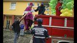 En esta fotografía del sábado 13 de julio de 2019, el obispo católico Rubén Darío Jaramillo Montoya es ayudado a subir a un camión de bomberos en Buenaventura, Colombia. Jaramillo viajó el sábado en ese camión a algunos de los vecindarios con mayor índice delictivo, rociando agua bendita en lo que dijo era un intento por frustrar las labores de los narcotraficantes y de otros grupos ilegales. (AP Foto/Fernando Vergara)