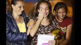 En esta fotografía´del martes 16 de julio de 2019, Karen Palacios, al centro, es ayudada por familiares después de que salió de la cárcel en Los Teques en las afueras de Caracas, Venezuela. Palacios, que toca el clarinete y fue despedida de la Filarmónica Nacional por criticar al gobierno, estuvo detenida 6 semanas. (AP Foto/Ariana Cubillos)