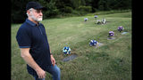 Eddie Davis stands beside the gravestone of his son Jeremy, furtherest left, who died from the abuse of opioids, Wednesday, July 17, 2019, in Coalton, Ohio. Members of his family are buried in adjacent plots, including his parents and a sibling. (AP Photo/John Minchillo)