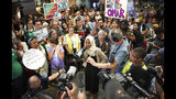 """U.S. Rep. Ilhan Omar speaks to supporters after arriving home, at Minneapolis–Saint Paul International Airport, Thursday, July 18, 2019, in Minnesota. President Donald Trump is chiding campaign supporters who'd chanted """"send her back"""" about Somali-born Omar, whose loyalty he's challenged. (Glen Stubbe/Star Tribune via AP)"""