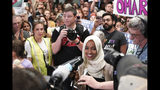 """U.S. Rep. Ilhan Omar speaks to supporters as she arrives at Minneapolis–Saint Paul International Airport, Thursday, July 18, 2019, in Minnesota. President Donald Trump is chiding campaign supporters who'd chanted """"send her back"""" about Somali-born Omar, whose loyalty he's challenged. (Glen Stubbe/Star Tribune via AP)"""