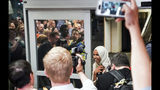 """U.S. Rep. Ilhan Omar reacts as she's greeted by supporters cheering """"Welcome Home Ilhan!"""" as she arrived home at Minneapolis–Saint Paul International Airport, Thursday, July 18, 2019, in Minnesota. President Donald Trump is chiding campaign supporters who'd chanted """"send her back"""" about Somali-born Omar, whose loyalty he's challenged. (Glen Stubbe/Star Tribune via AP)"""