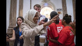 Rep. Ilhan Omar, D-Minn., a target of racist rhetoric from President Donald Trump, is cheered by visitors as she walks from the House to her office following votes, at the Capitol in Washington, Thursday, July 18, 2019. (AP Photo/J. Scott Applewhite)