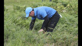 Northern Ireland's Rory McIlroy looks for his ball in the long rough on the 1st hole during the first round of the British Open Golf Championships at Royal Portrush in Northern Ireland, Thursday, July 18, 2019.(AP Photo/Peter Morrison)